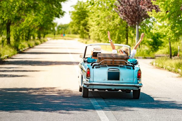 Happy Mature Couple leaving for a Romantic Road trip Vacation with a Vintage car